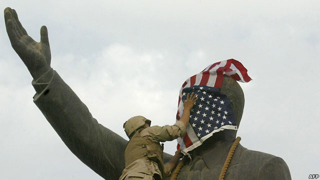Solider covers a statues face with an American flag