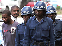 Zimbabwe's riot policemen walk on a Harare street