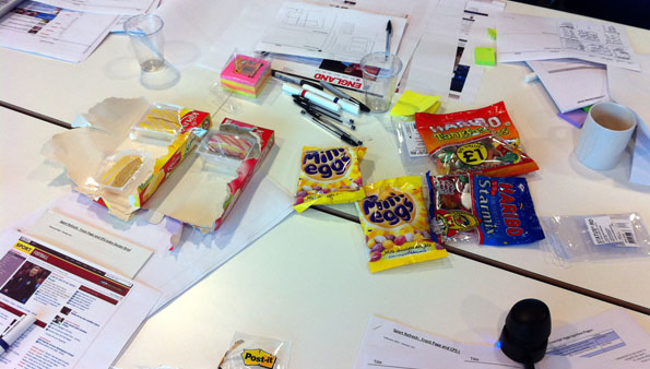 Design mockups, documents, and sugary sweets scattered across a white meeting room table.