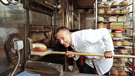 Michel Roux Jr removing bread from a traditional baker's oven.
