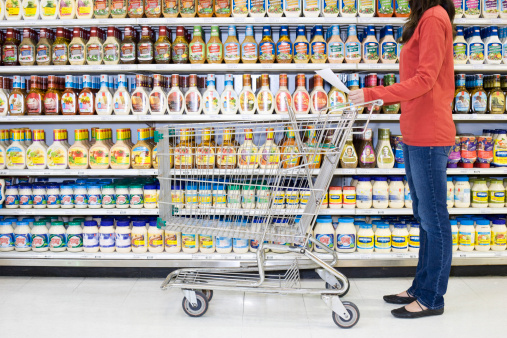 Consumer choosing mayonnaise from supermarket shelf.
