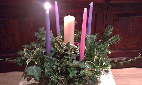 Angela's Advent Wreath has five candles with holly and other leaves ...
