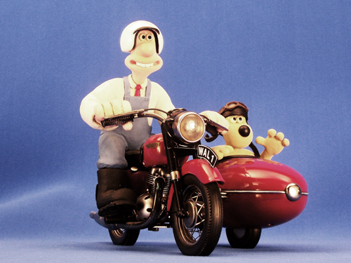 Wallace and Gromit on a bike, being filmed in front of a blue screen