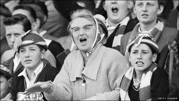Supporters watch a football match in 1962