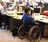 Workplace with man in a wheelchair working at a desk next to an able-bodied colleague