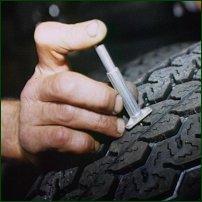A mechanic testing a tyre's tread depth.