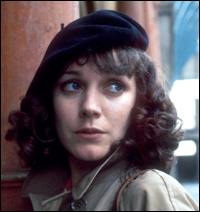 A beret-clad Jan Francis as Lisa Colbert, looking scared and furtive.