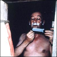 Reporter Allan Little shaving in Sierra Leone.
