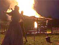Photograph from a historical reconstruction, two figures stand in front of a burning house