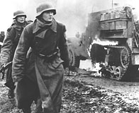 Two German soldiers and a burning US vehicle