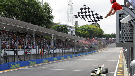Jenson Button taking the chequered flag at the Brazilian Grand Prix last year, when he claimed the world title
