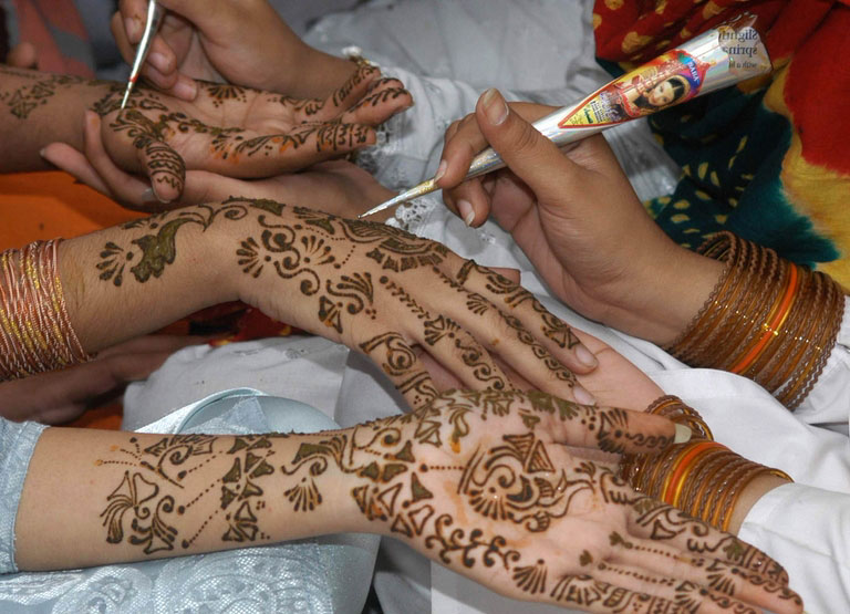 Pakistani girls make patterns with henna, in Multan, Pakistan on Saturday, Nov. 13, 2004 in preparation for Eid al-Fitr, festival to mark the end of the Muslim holy fasting month of Ramadan. (AP Photo/Khalid Tanveer)