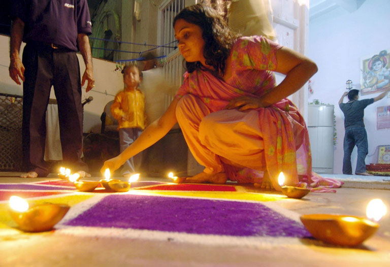 A Pakistani Hindu girl (R) is watched by her family as she lights clay 'diyas' (earthen lamps) at her home in Karachi, 01 November 2005, during celebrations of the Hindu Festival of Diwali. The festival marks the home coming of the Hindu God, Lord Rama after killing the evil King Ravana, symbolising the victory of good over evil and leading the people from darkness to light. ASIF HASSAN/AFP/Getty Images