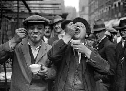 Two men enjoy jellied eels in a Whitechapel street on a Sunday morning.