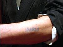 Holocaust survivor with number tattooed on forearm