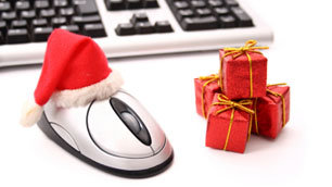 A computer mouse decorated with a Santa hat, beside a small gift, illustrating online shoppin