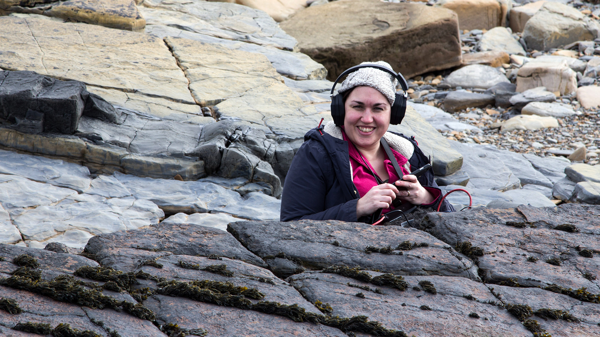 Sound designer Catherine Robinson hides behind a rock while filming in Orkney