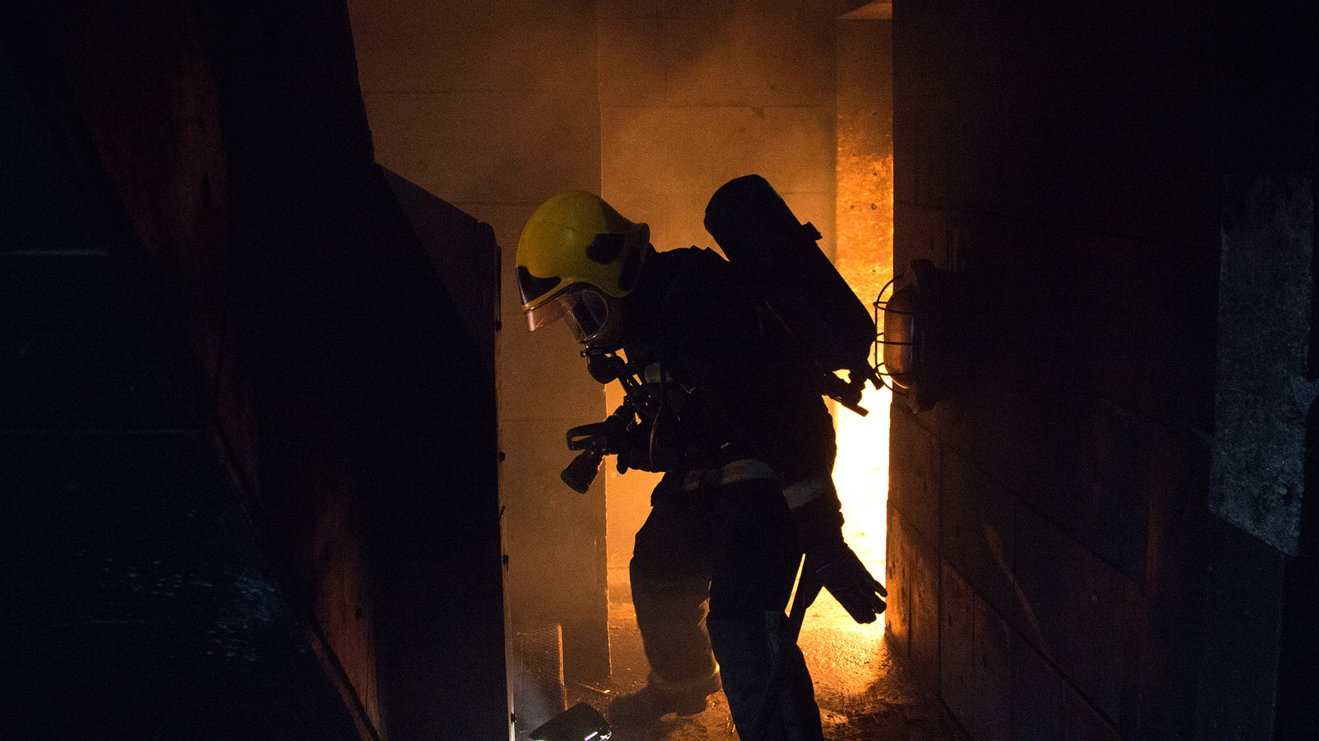 A firefighter walking towards a staircase with flames behind