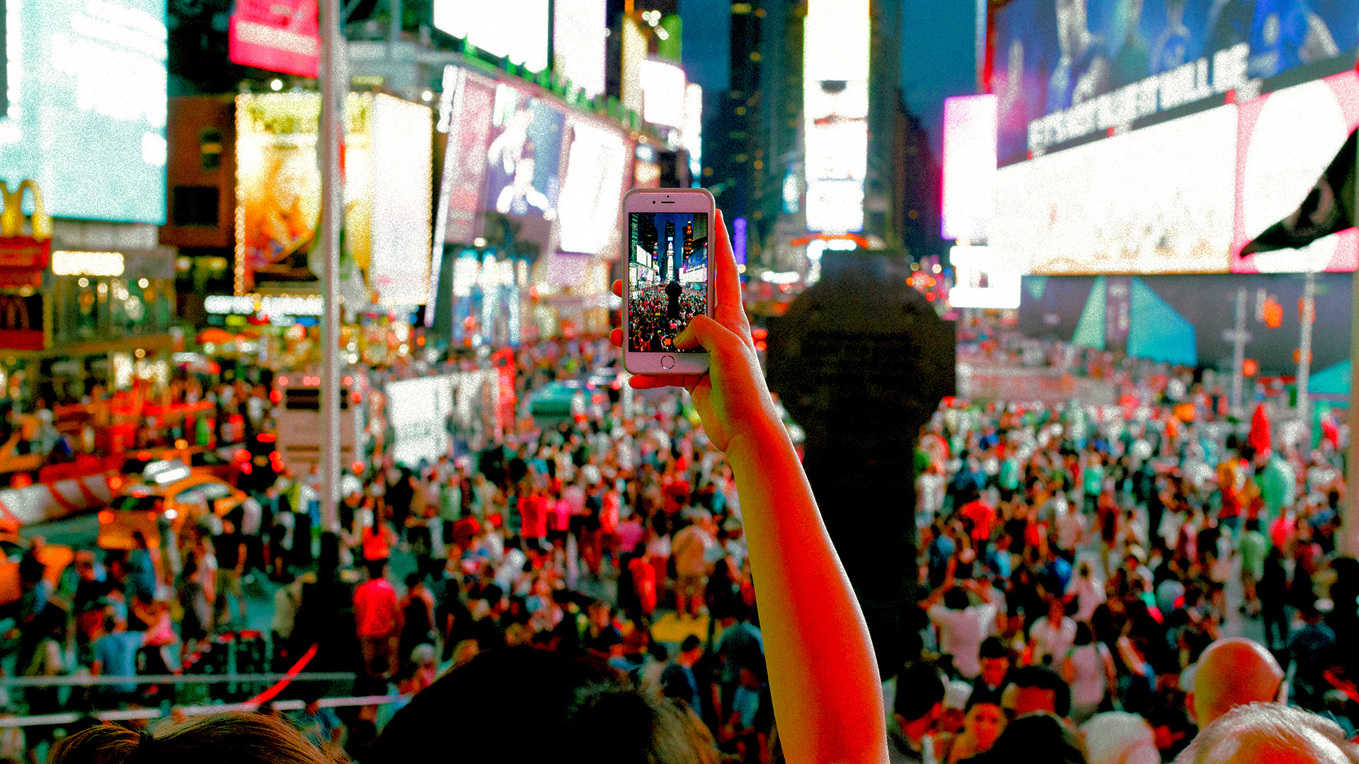 A smartphone filming a crowd in Times Square in New York