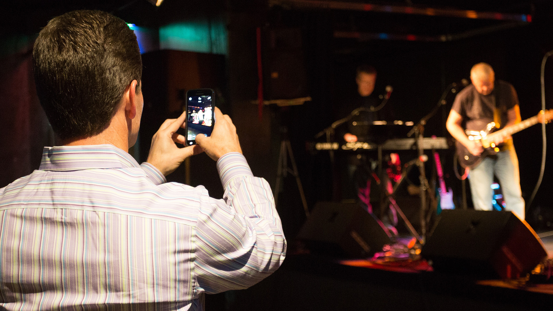 A man films a concert on his smartphone.