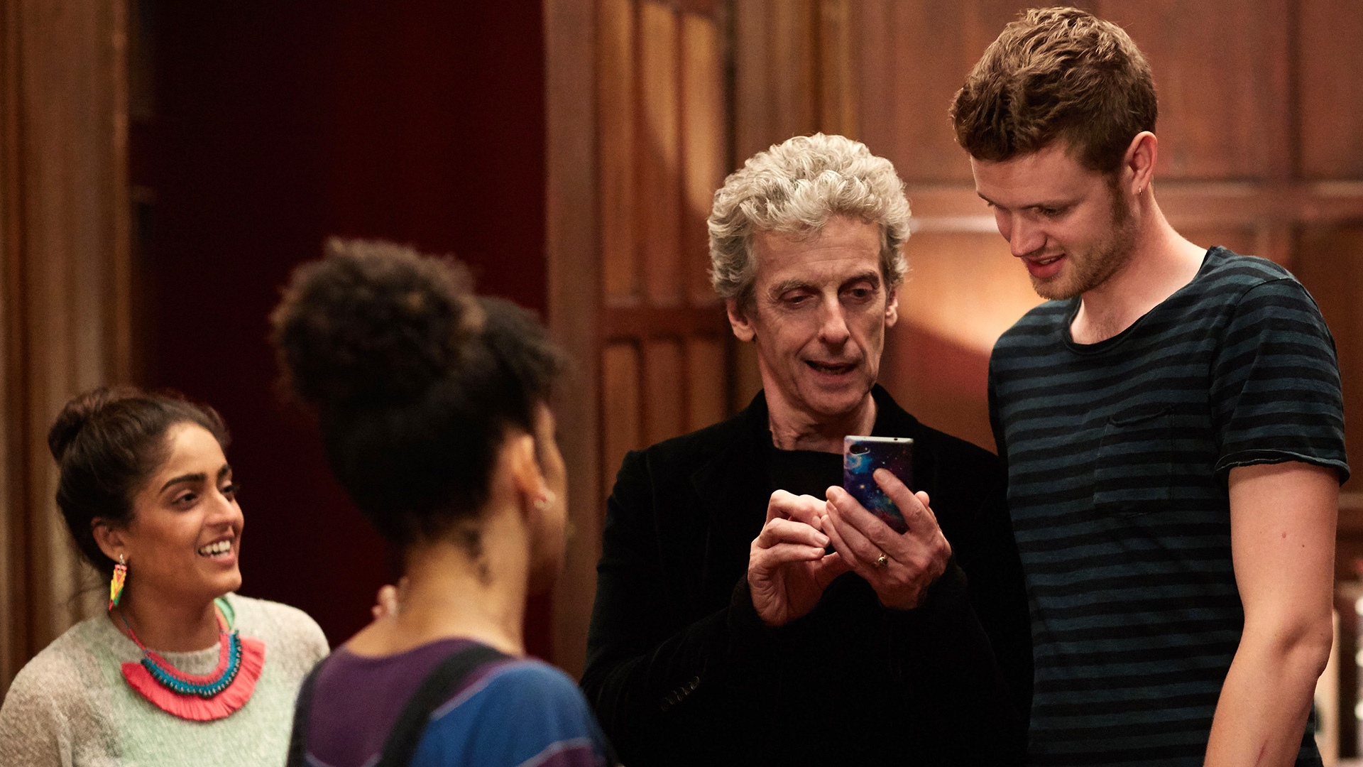 A scene from Doctor Who - the Doctor is showing a young man something on his mobile phone.