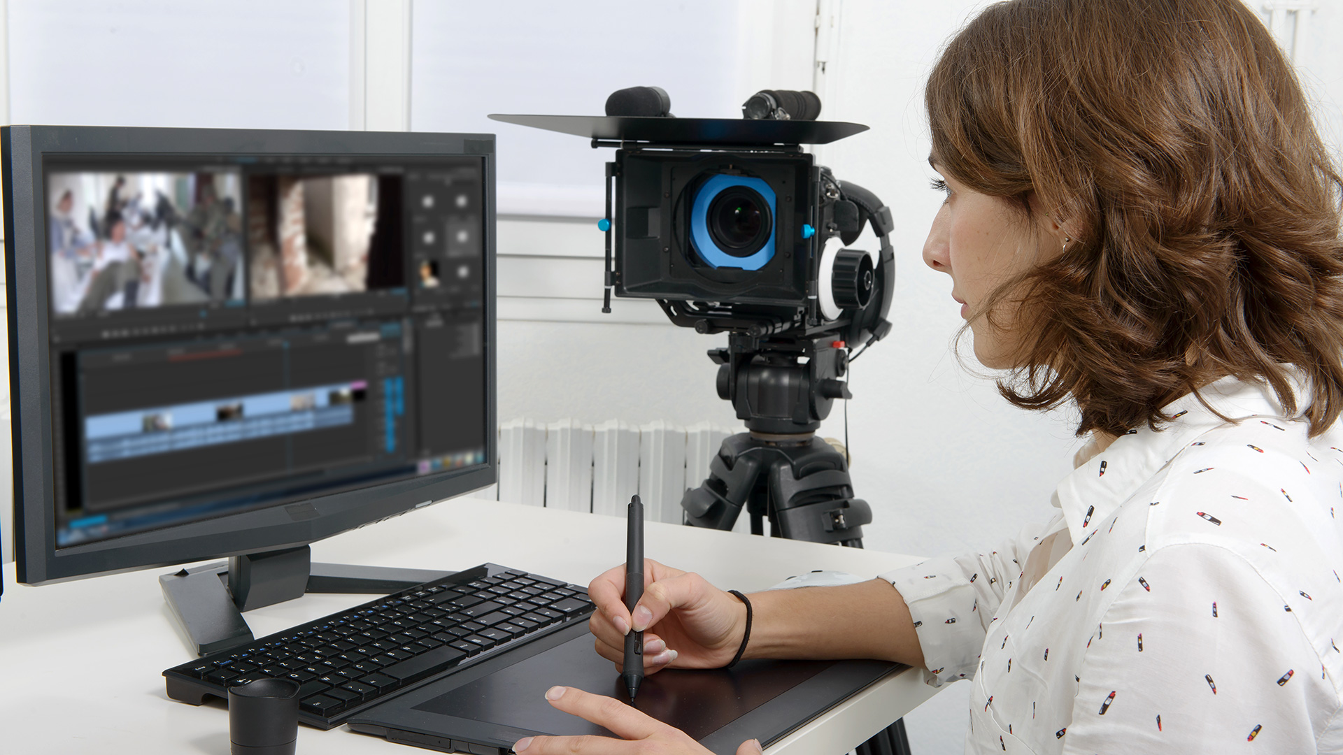A woman edits video footage at a computer.