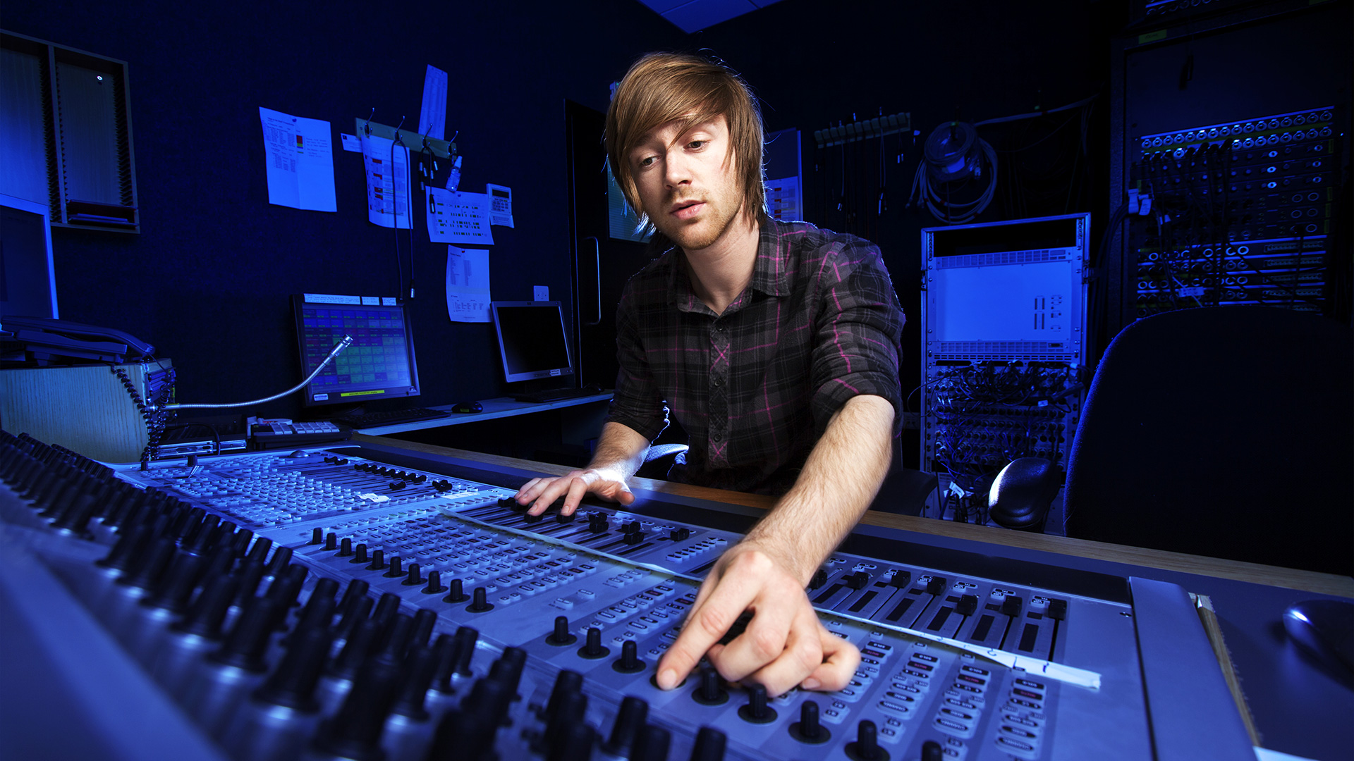 A man is at a mixing desk in a darkly lit studio.