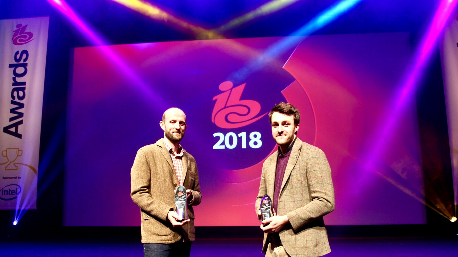 Craig Wright and David Johnston on stage at the IBC Awards with their trophies.