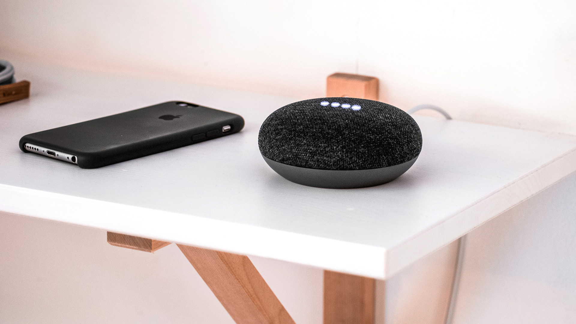 A smart speaker and phone placed next to each other on a shelf.