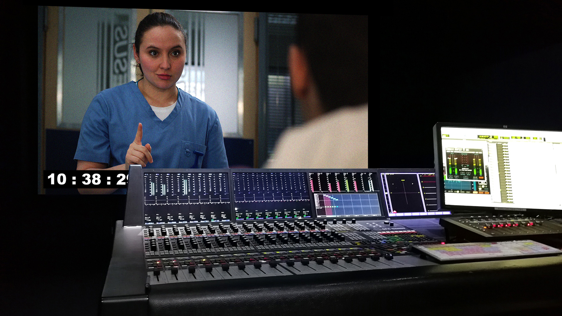 A mixing desk in an editing studio, with a scene from BBC's Casualty playing on a monitor