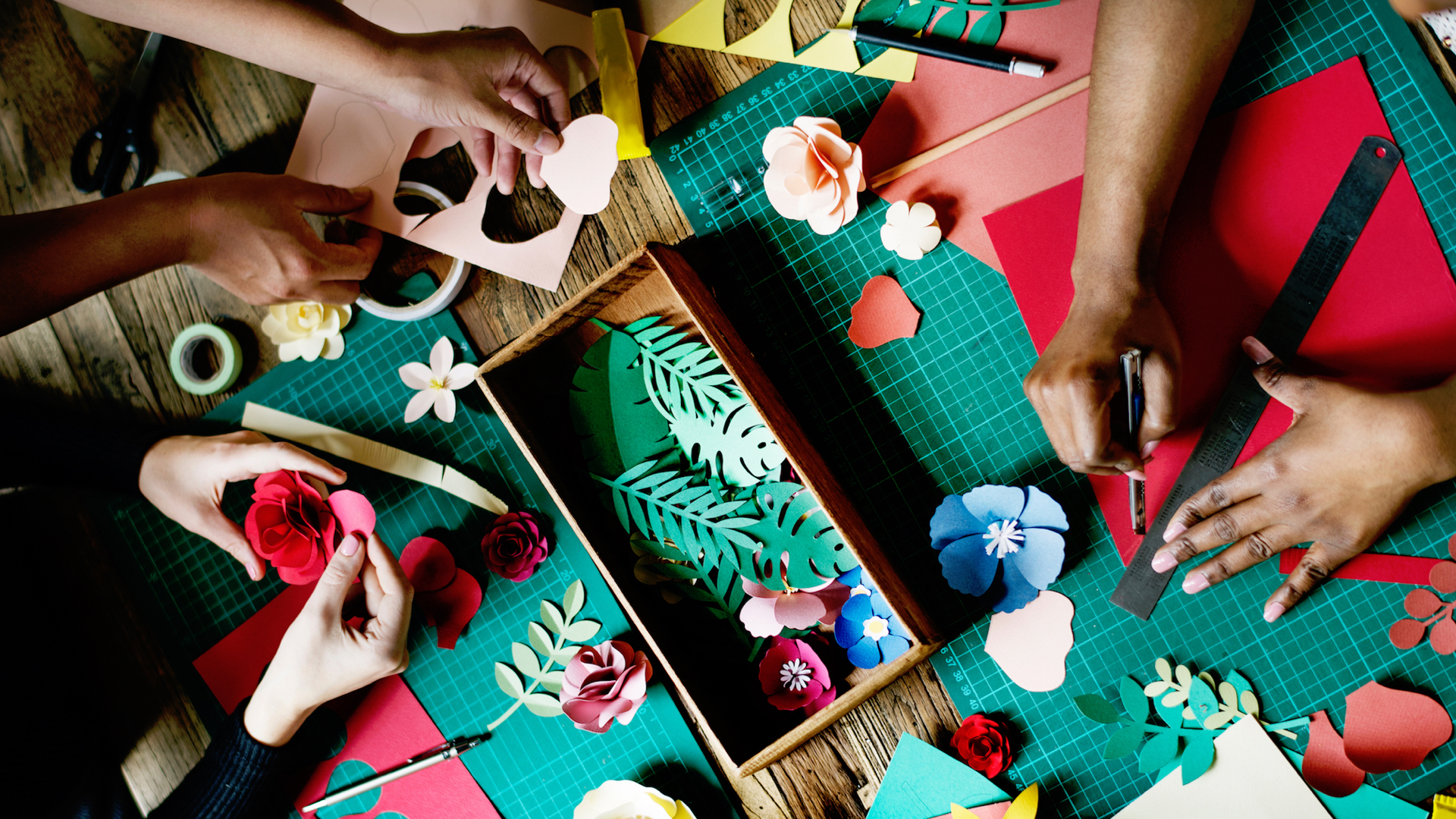 People being creative, making things with paper and craft materials on a table.