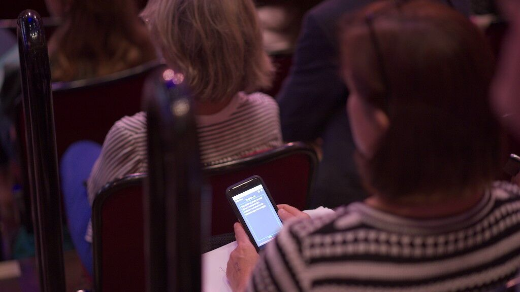 A member of the audience using the Notes app on their phone.