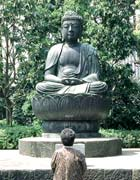 Japanese woman standing in front of a statue of Buddha