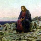 Jesus sitting alone in the desert in an attitude of prayer
