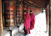 Robed Tibetan monks at Little Tibet, Xiahe, Guangshu, China, turning huge prayer wheels mounted along a wall