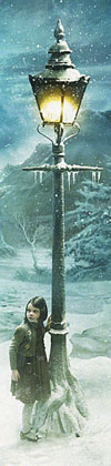 Lucy Pevensie (Georgie Henley) by the lamppost in a snowy wood.