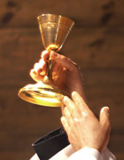 Priest's hand holding chalice at communion