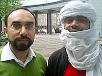 Heart and Soul presenter Navid Akhtar with Abdullah Ag Alhousseyni, a North African Tuareg man wearing a headscarf that covers all of his head except for his face from the eyebrows down to the mouth