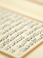 Arabic writing visible on the page of a Qur'an