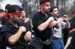 Shi'a men wearing red headbands in an Ashura parade