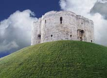 Round stone castle keep on a motte (mound of earth)