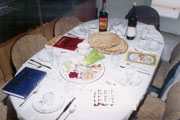 Table with seder meal and Haggadah by every place
