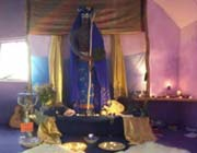 Soft lighting, mats and decorations surround an altar and statue of the Goddess