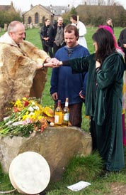 Male and female druids performing a marriage ceremony for a couple at Avebury stone circle