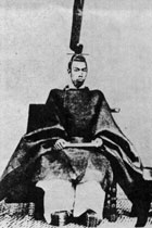 Emperor Meiji sitting in his full court robes. Extremely wide sleeves and wide trousers are visible and he is wearing a very tall and narrow hat