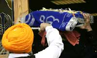 The Sikh holy book, wrapped in embroidered cloth, is carried through the temple door