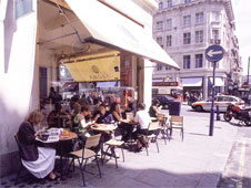 People sit outside in a street cafe in central London