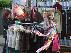 A clothes stall on the market in Eastenders. Kat and Ruby arrange clothes on the stall.