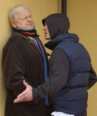 An old man being threatened by a hooded youth