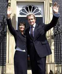 A fictional British prime minister and his wife standing outside 10 Downing street